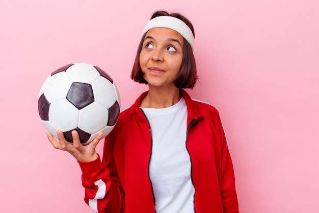 Junge mischlingsfrau, die fußball spielt, der auf rosa hintergrund lokalisiert wird, der vom erreichen von zielen und zwecken träumt