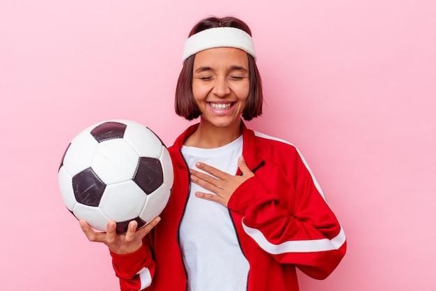 Junge mischlingsfrau, die fußball spielt, der auf rosa hintergrund lokalisiert wird, lacht laut und hält hand auf brust.