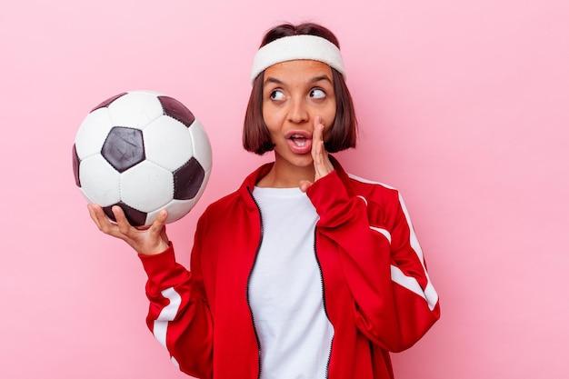 Junge mischlingsfrau, die fußball spielt, der auf rosa wand isoliert wird, sagt eine geheime heiße bremsnachricht und schaut zur seite