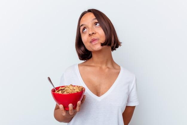 Junge mischlingsfrau, die getreide isst, das auf weißem hintergrund lokalisiert wird und davon träumt, ziele und zwecke zu erreichen