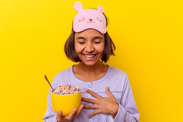 Junge mischlingsfrau, die müsli isst, die einen pijama tragen, der auf gelbem hintergrund lokalisiert wird, der lacht und spaß hat.