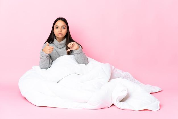 Junge mischlingsfrau, die pijama trägt, die auf dem boden sitzt, der gutes-schlechtes zeichen macht. unentschieden zwischen ja oder nicht