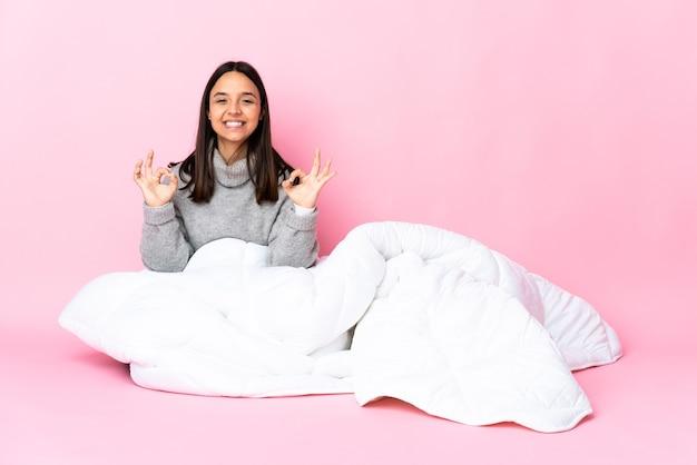 Junge mischlingsfrau, die pijama trägt, die auf dem boden sitzt und ok zeichen mit zwei händen zeigt