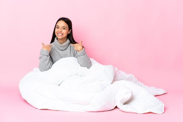 Junge mischlingsfrau, die pijama trägt, sitzt auf dem boden und gibt eine daumen hoch geste