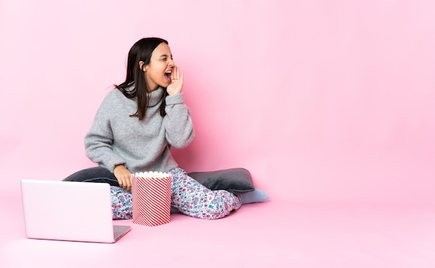 Junge mischlingsfrau, die popcorn isst, während sie einen film sieht