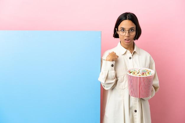Junge mischlingsfrau, die popcorn mit einem großen banner hält, isolierter hintergrund, der auf sich selbst zeigt