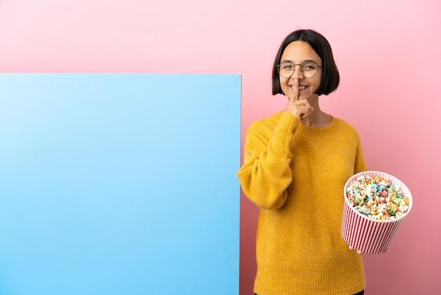 Junge mischlingsfrau, die popcorn mit einem großen banner über isoliertem hintergrund hält, das ein zeichen der stille zeigt, die den finger in den mund steckt