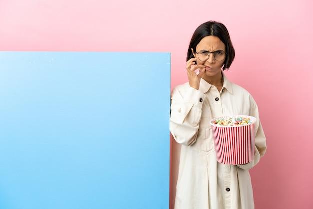 Junge mischlingsfrau, die popcorn mit einem großen banner über isoliertem hintergrund hält, das ein zeichen der stille zeigt