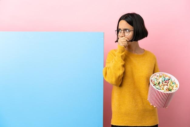 Junge mischlingsfrau, die popcorn mit einem großen banner über isoliertem hintergrund hält, der den mund bedeckt und zur seite schaut