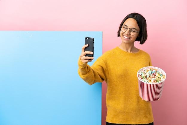 Junge mischlingsfrau, die popcorns mit einem großen banner über lokalisiertem hintergrund hält, der ein selfie macht