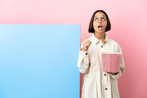 Junge mischlingsfrau, die popcorns mit einem großen banner über lokalisiertem hintergrund hält, der oben und überrascht zeigt Premium Fotos