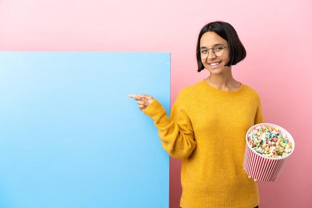 Junge mischlingsfrau, die popcorns mit einem großen banner über lokalisiertem hintergrund hält, der zurück zeigt