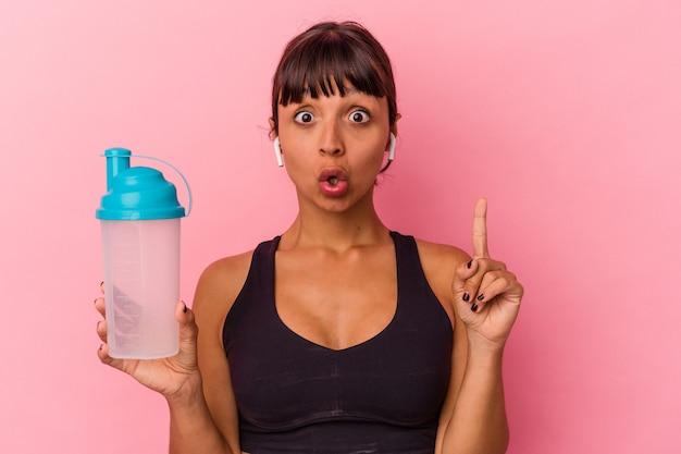 Junge mischlingsfrau, die proteinshake trinkt, einzeln auf rosafarbenem hintergrund mit einer großartigen idee, konzept der kreativität.