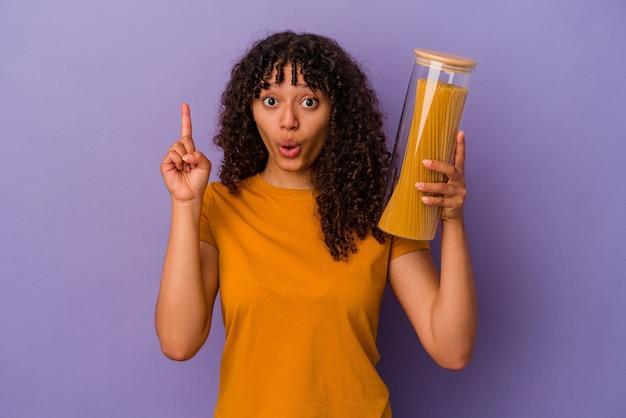 Junge mischlingsfrau, die spaghetti einzeln auf violettem hintergrund hält und eine großartige idee hat, konzept der kreativität.