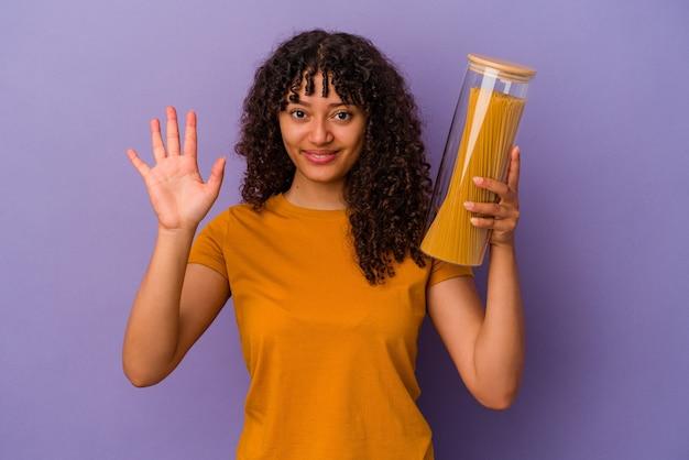 Junge mischlingsfrau, die spaghetti hält, die auf violettem hintergrund lokalisiert wird, lächelt fröhlich und zeigt nummer fünf mit den fingern