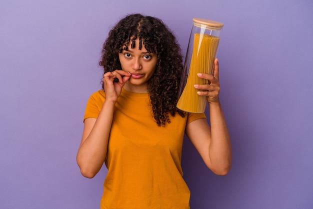 Junge mischlingsfrau, die spaghetti lokalisiert auf violettem hintergrund mit fingern auf lippen hält, die ein geheimnis halten.