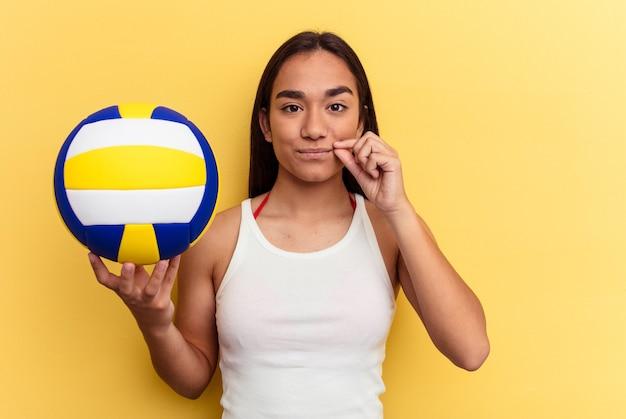 Junge mischlingsfrau, die volleyball am strand spielt, lokalisiert auf gelbem hintergrund mit fingern auf den lippen, die ein geheimnis halten.