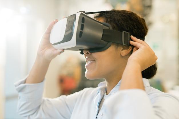 Junge mischlingsfrau, die vr headset auf kopf nimmt, um präsentation des neuen sortiments zu sehen und produkt zu wählen