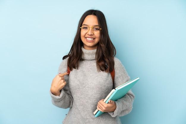 Junge mischlingsfrau, die zur blauen wand stolz und selbstzufrieden zur schule geht