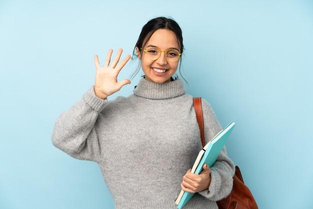 Junge mischlingsfrau, die zur schule auf blauer wand geht, die fünf mit den fingern zählt