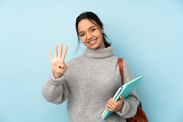 Junge mischlingsfrau, die zur schule auf blauer wand glücklich geht und vier mit den fingern zählt