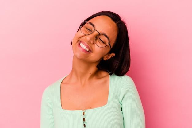 Junge mischlingsfrau isoliert auf rosa entspanntem und glücklichem lachen, gestreckter hals zeigt zähne.