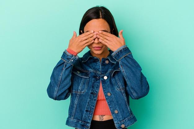 Junge mischlingsfrau lokalisiert auf blauem ängstlichem bedecken der augen mit händen.