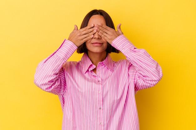 Junge mischlingsfrau lokalisiert auf gelbem hintergrund angst, die augen mit den händen zu bedecken.