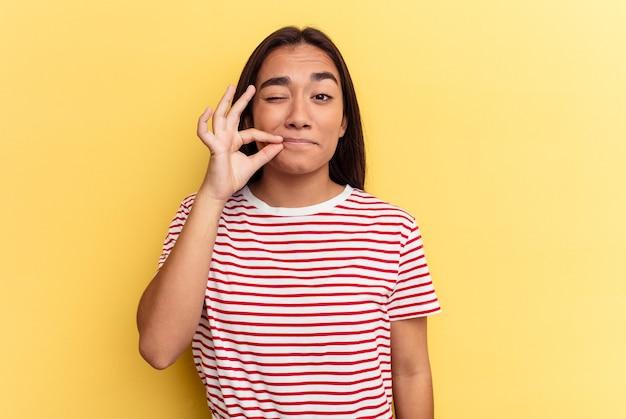 Junge mischlingsfrau lokalisiert auf gelbem hintergrund mit den fingern auf den lippen, die ein geheimnis halten.