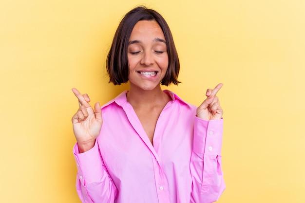 Junge mischlingsfrau lokalisiert auf gelber wand, die finger kreuzt, um glück zu haben