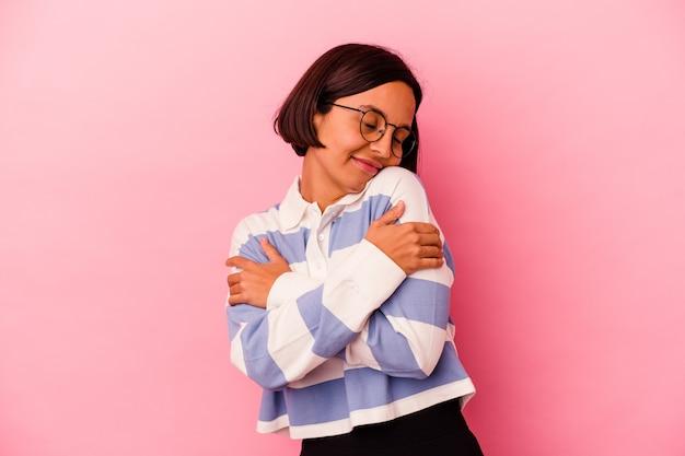 Junge mischlingsfrau lokalisiert auf rosa hintergrundumarmungen, lächelnd sorglos und glücklich.