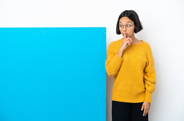 Junge mischlingsfrau mit einem großen blauen plakat isoliert auf weißem hintergrund, das ein zeichen der stille zeigt, geste, die finger in den mund steckt