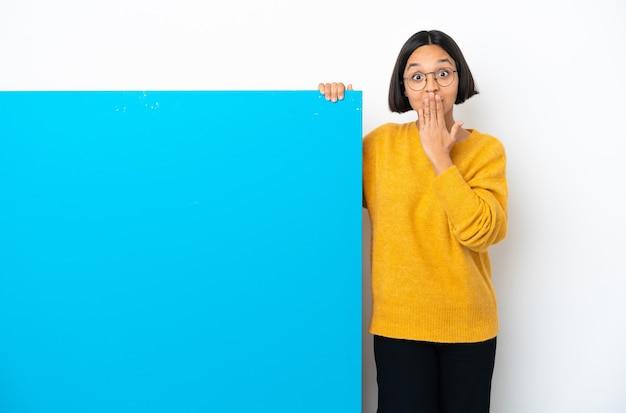 Junge mischlingsfrau mit einem großen blauen plakat lokalisiert auf weißem hintergrund, der den mund mit der hand bedeckt
