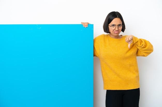 Junge mischlingsfrau mit einem großen blauen plakat lokalisiert auf weißem hintergrund, der gut-schlecht-zeichen macht. unentschlossen zwischen ja oder nicht