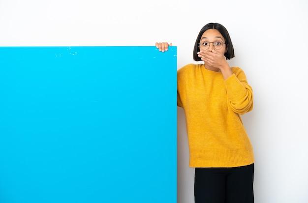 Junge mischlingsfrau mit einem großen blauen plakat lokalisierte, das den mund mit der hand bedeckt