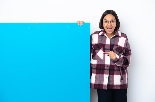 Junge mischlingsfrau mit einem großen blauen plakat lokalisierte überraschte und zeigende seite