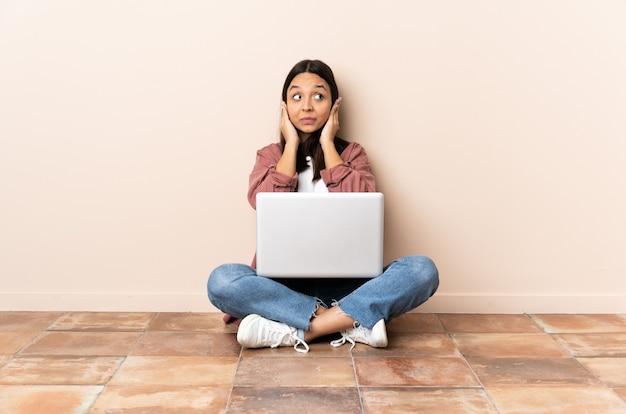 Junge mischlingsfrau mit einem laptop, der auf dem boden sitzt, frustriert