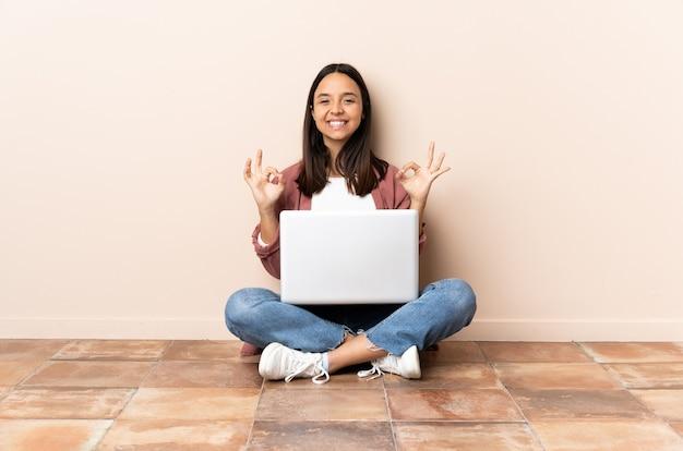 Junge mischlingsfrau mit einem laptop, der auf dem boden sitzt und ok zeichen mit zwei händen zeigt