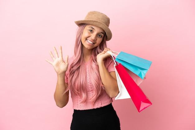Junge mischlingsfrau mit einkaufstasche einzeln auf rosa hintergrund, die fünf mit den fingern zählt