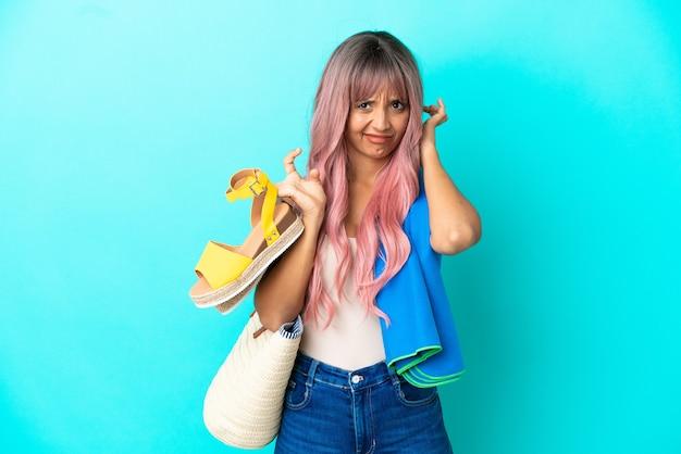 Junge mischlingsfrau mit rosa haaren, die sommersandalen isoliert auf blauem hintergrund mit zweifeln hält
