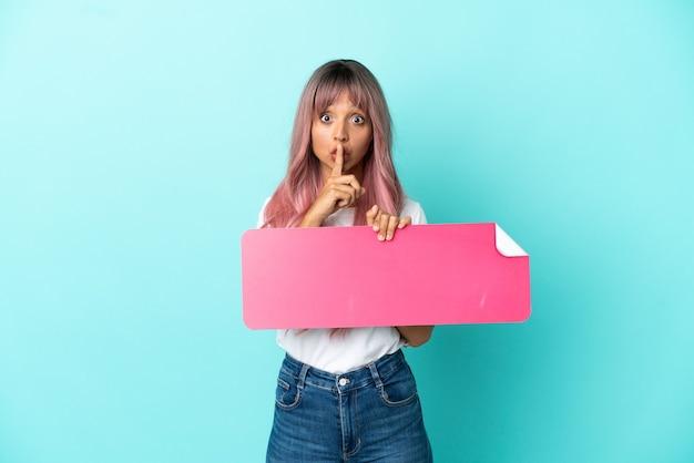 Junge mischlingsfrau mit rosa haaren einzeln auf blauem hintergrund, die ein leeres plakat hält, das stillegeste tut