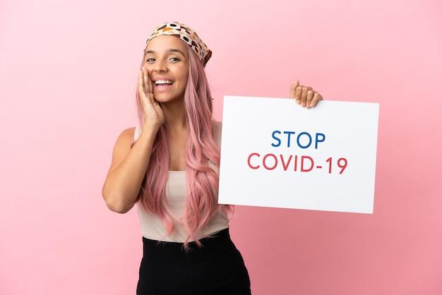 Junge mischlingsfrau mit rosa haaren einzeln auf rosafarbenem hintergrund, die ein plakat mit dem text stop covid 19 halten und schreien