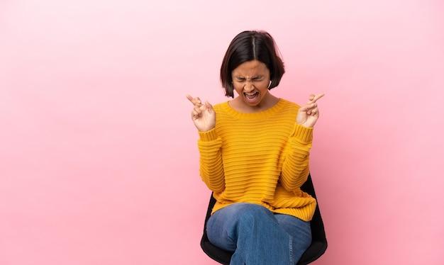 Junge mischlingsfrau sitzt auf einem stuhl, isoliert mit gekreuzten fingern