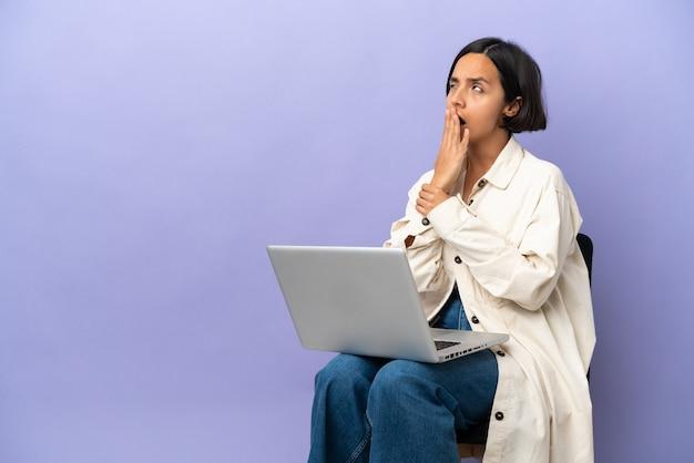 Junge mischlingsfrau sitzt auf einem stuhl mit laptop isoliert auf violettem hintergrund, gähnt und bedeckt den weit geöffneten mund mit der hand