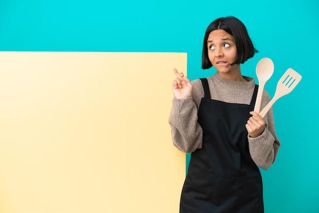 Junge mischlingskochfrau mit einem großen plakat, das mit gekreuzten fingern isoliert ist und das beste wünscht