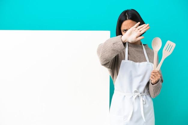 Junge mischlingskochfrau mit einem großen plakat einzeln auf blauem hintergrund, das mit ihrer hand eine stoppgeste macht, um eine handlung zu stoppen