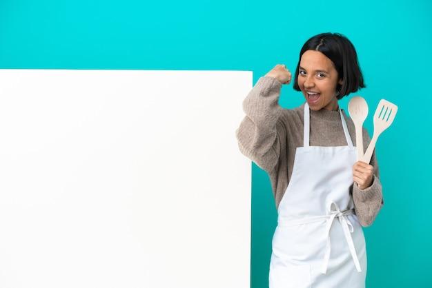 Junge mischlingskochfrau mit einem großen plakat lokalisiert auf blauem hintergrund, das starke geste tut