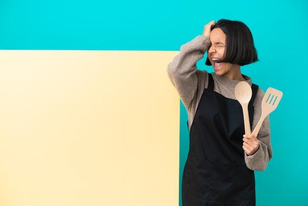 Junge mischlingskochfrau mit einem großen plakat lokalisiert auf blauem hintergrund gestresst überwältigt