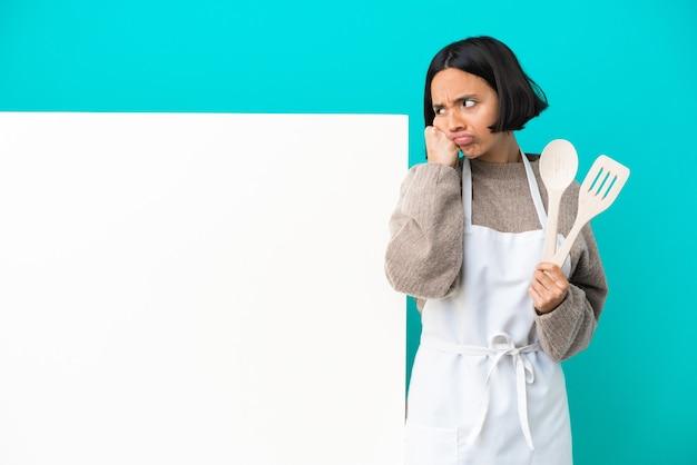 Junge mischlingskochfrau mit einem großen plakat lokalisiert auf blauem hintergrund mit müdem und gelangweiltem ausdruck