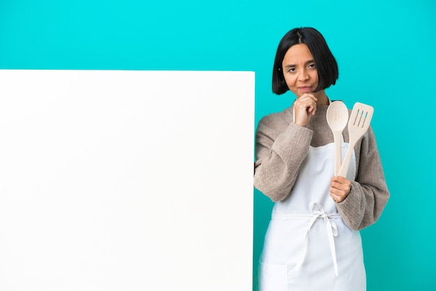 Junge mischlingskochfrau mit einem großen plakat lokalisiert auf blauem hintergrunddenken
